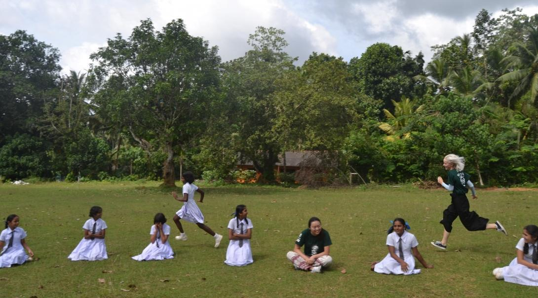 A volunteer doing community work in Sri Lanka with a group, runs outside with children during a game.